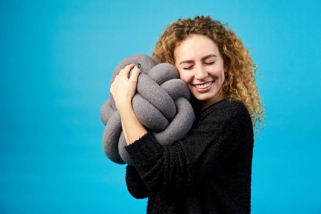 Jovem atraente sorridente alegre gengibre encaracolado abraça um brinquedo macio com prazer.