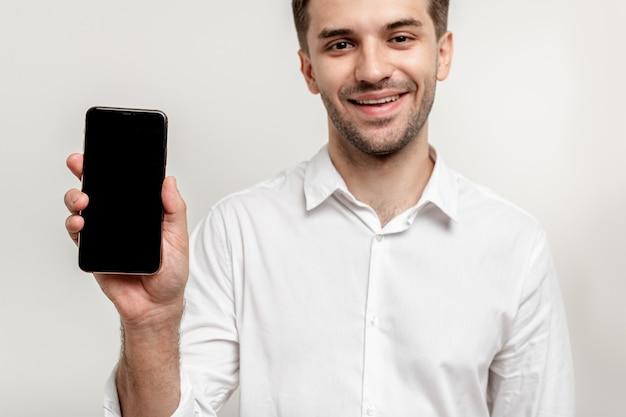 Jovem atraente sorridente em camisa branca mostrando celular foco no celular close-up isolado