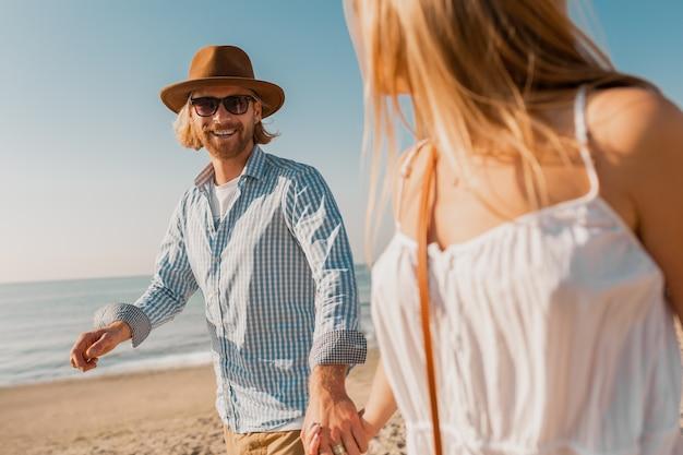 Jovem atraente sorridente feliz com chapéu e mulher loira com vestido branco correndo juntos na praia