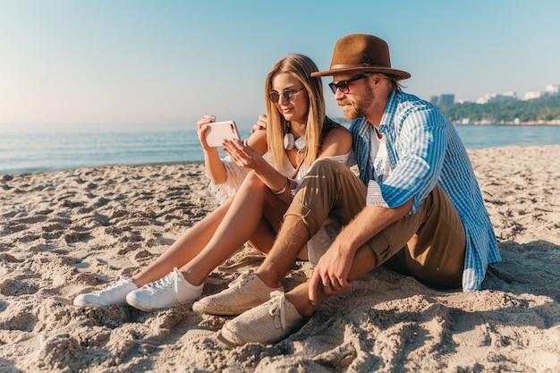Jovem atraente sorridente, feliz, homem e mulher com óculos de sol, sentado na praia de areia tirando foto de selfie