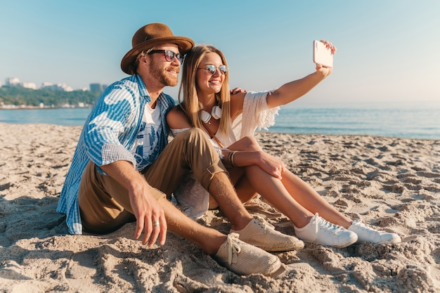 Jovem atraente sorridente, feliz, homem e mulher em óculos de sol, sentado na praia de areia, tirando foto de selfie