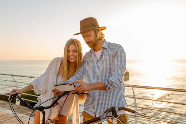 Jovem atraente sorridente feliz homem e mulher viajando de bicicleta usando smartphone, casal romântico à beira-mar no pôr do sol, roupa de estilo boho hipster, amigos se divertindo juntos
