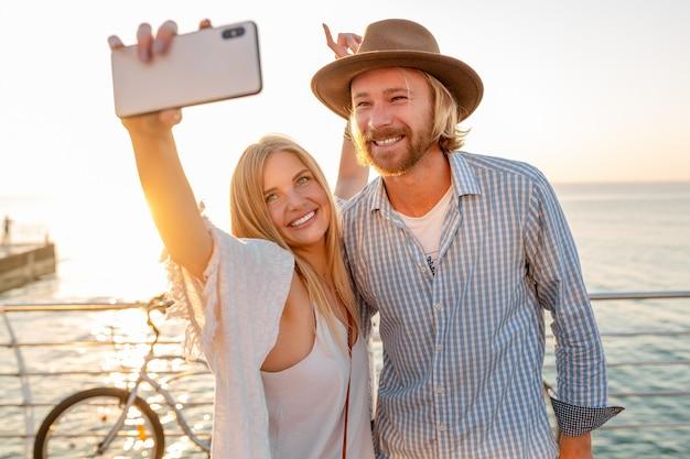 Jovem atraente sorridente homem feliz e mulher viajando de bicicleta tirando foto de selfie na câmera do telefone, casal romântico à beira-mar no pôr do sol, roupa estilo boho hipster, amigos se divertindo juntos