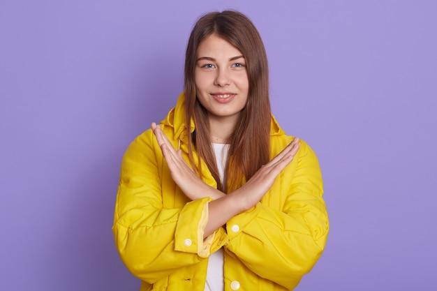 Jovem atraente sorridente, mantém os braços cruzados, mostrando o gesto proibitivo isolado sobre o fundo lilás, olha para a câmera, tem cabelo longo e reto, vestindo jaqueta amarela casual.