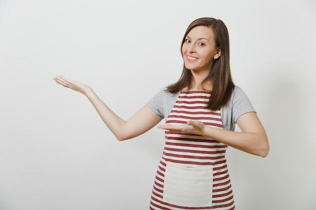 Jovem atraente sorridente morena caucasiana dona de casa no avental listrado isolada. linda dona de casa apontando as duas mãos para o lado