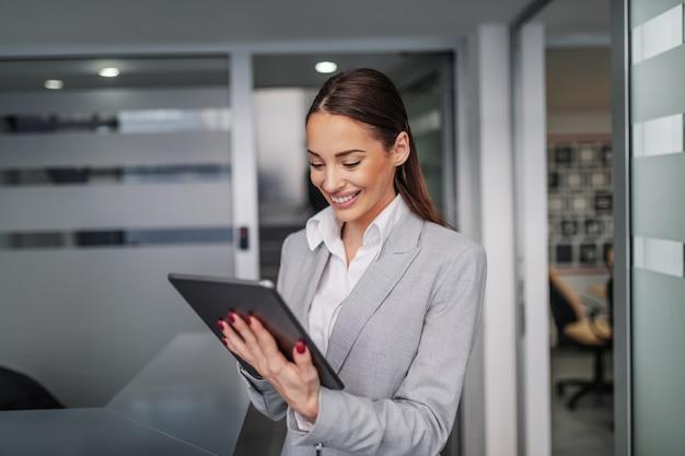 Jovem atraente sorridente morena caucasiana em terno de pé no corredor e usando o tablet. conceito de negócios corporativos.