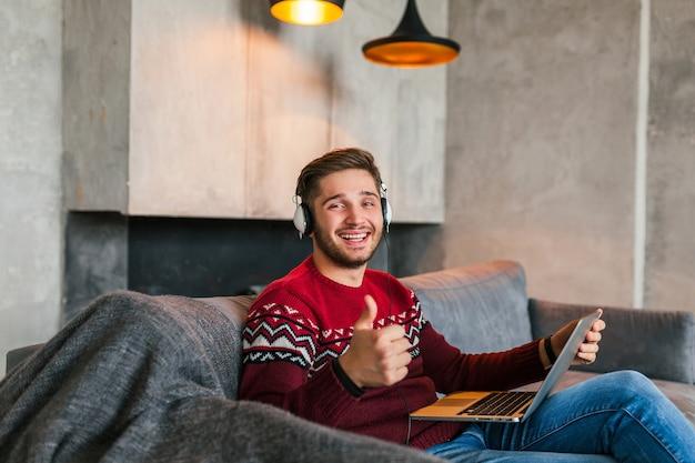Jovem atraente sorridente no sofá em casa no inverno em fones de ouvido, vestindo um suéter vermelho de malha, trabalhando no laptop, freelancer, feliz, positivo, aparecendo o polegar