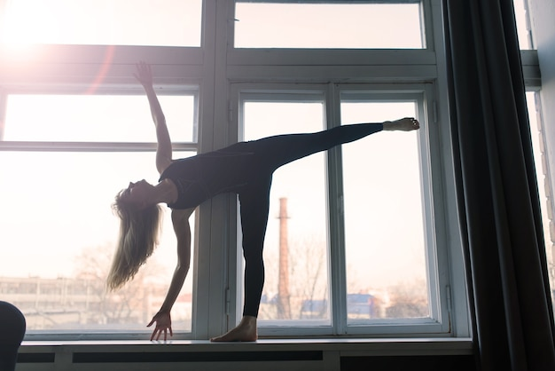 Jovem atraente sorridente praticando ioga, malhando, vestindo roupas esportivas, sutiã, treinamento em casa