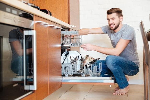 Jovem atraente sorridente usando a máquina de lavar louça na cozinha de casa