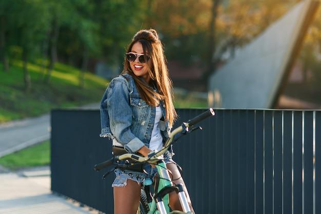 Jovem atraente tentadora em roupas da moda jeans usa óculos elegantes, sentado na bicicleta e posando na câmera na noite de verão.