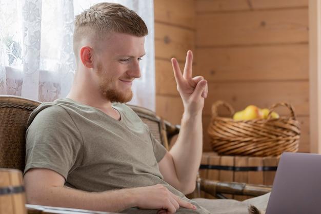 Jovem atraente trabalha com laptop, comunica-se em redes sociais, gesticulando com o sinal de v, em casa de madeira com cesto de maçãs amarelas e conceito de trabalho remoto de cortina branca