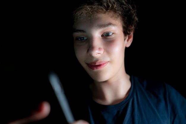 Jovem atraente usar telefone celular tarde da noite em um quarto escuro