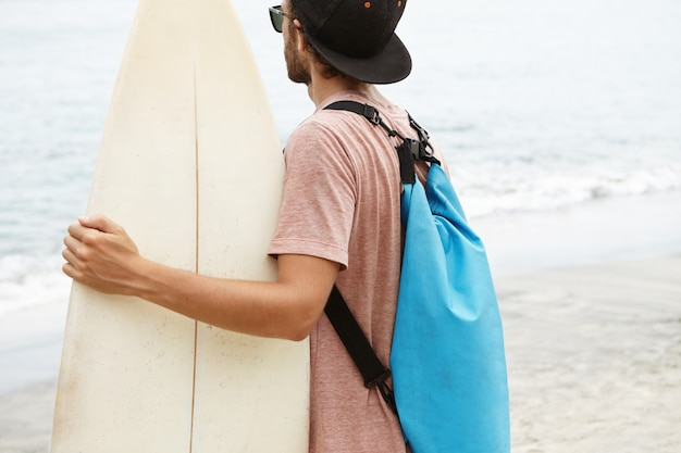 Jovem atraente vestido casualmente, vestindo snapback e óculos de sol, segurando sua prancha branca e olhando para o mar. surfista iniciante se preparando para o treinamento