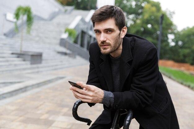 Jovem atraente vestido com um casaco encostado em uma bicicleta na rua, usnig celular
