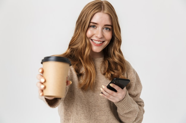Jovem atraente vestindo um suéter isolado na parede branca, bebendo café para viagem enquanto usa o telefone celular