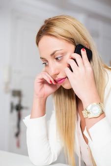 Jovem atraente wattractive jovem com longos cabelos loiros fala seriamente por telefone. mulher falando no telefone