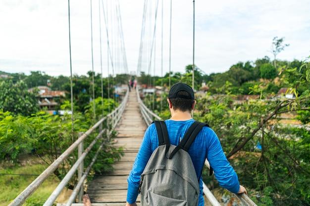 Jovem atravessando a ponte velha de madeira sobre o rio de uma vila na selva de sumatra
