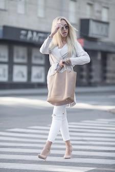 Jovem atravessando uma rua da cidade no dia de verão ensolarado