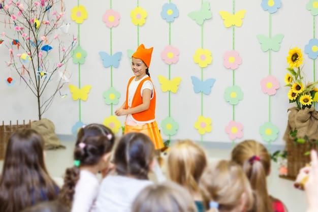 Jovem atriz com fantasia de raposa falando na frente de crianças