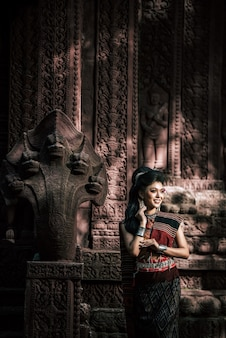 Jovem atriz vestindo lindos trajes antigos, em monumentos antigos, estilo dramático. interprete uma história popular de amor, lenda, um conto popular tailandês chamado