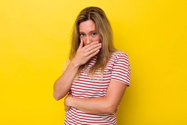 Jovem australiana isolada cobrindo a boca com as mãos parecendo preocupadas.