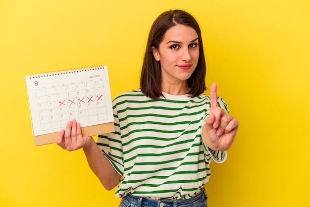 Jovem australiana segurando um calendário isolado em um fundo amarelo, mostrando o número um com o dedo.
