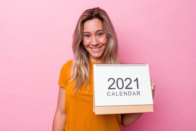 Jovem australiana segurando um calendário isolado no fundo rosa feliz, sorridente e alegre.