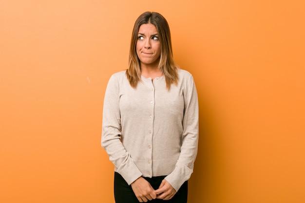 Jovem autêntica carismática mulher real contra uma parede confusa, sente-se duvidosa e insegura.