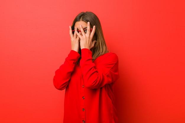 Jovem autêntica carismática mulher real contra uma parede piscar através dos dedos, assustada e nervosa.