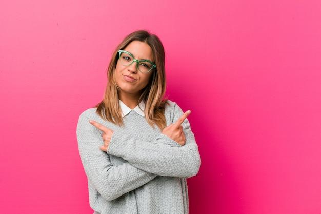 Jovem autêntica carismática pessoas reais mulher contra uma parede aponta de lado, está tentando escolher entre duas opções.