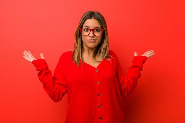 Jovem autêntica carismática pessoas reais mulher contra uma parede duvidando e encolher os ombros os ombros em gesto de questionamento.
