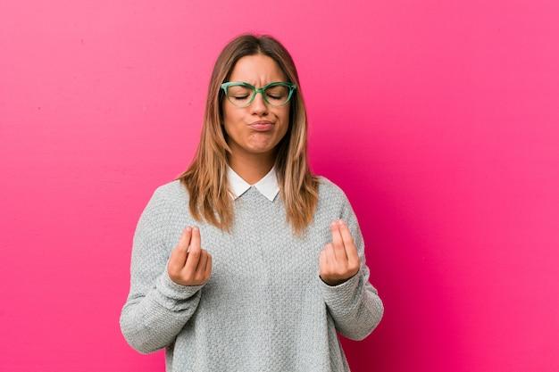 Jovem autêntica carismática pessoas reais mulher contra uma parede, mostrando que ela não tem dinheiro.