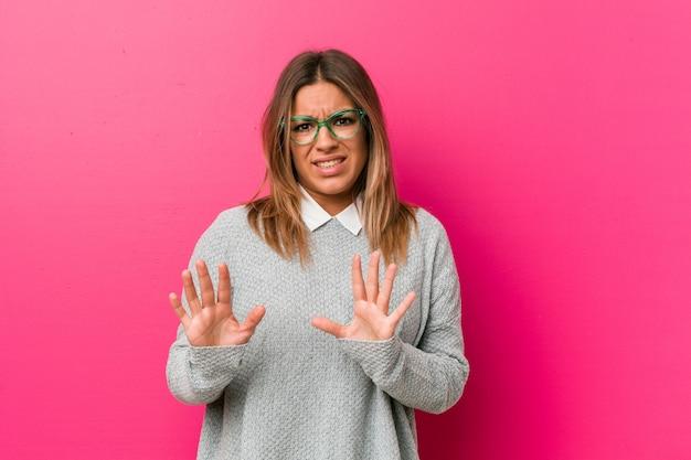 Jovem autêntica carismática pessoas reais mulher contra uma parede, rejeitando alguém mostrando um gesto de nojo.