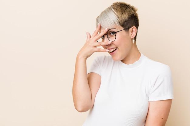 Jovem autêntica mulher natural vestindo uma camisa branca pisca entre os dedos, rosto com vergonha de cobertura