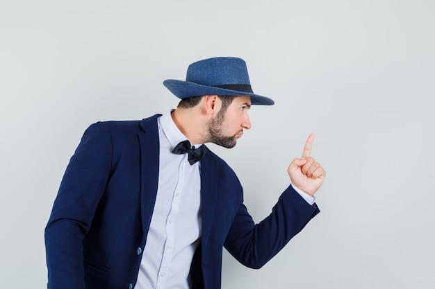 Jovem avisando alguém com o dedo no terno, chapéu e parecendo nervoso, vista frontal.