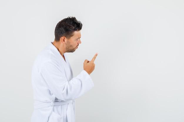 Jovem avisando alguém com um gesto do dedo no roupão branco e parecendo nervoso, vista frontal.