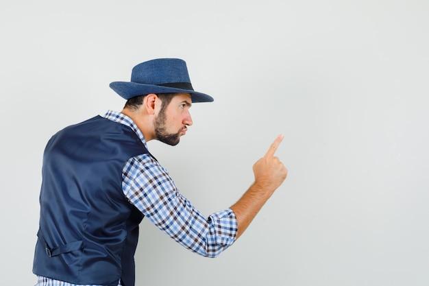 Jovem avisando com o dedo na camisa, colete, chapéu e olhando com raiva. .
