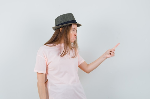 Jovem avisando com o dedo no chapéu rosa e parecendo rancorosa
