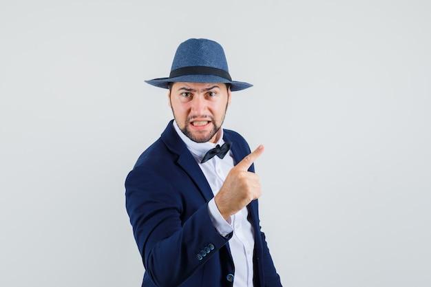 Jovem avisando com o dedo no terno, chapéu e parecendo nervoso. vista frontal.