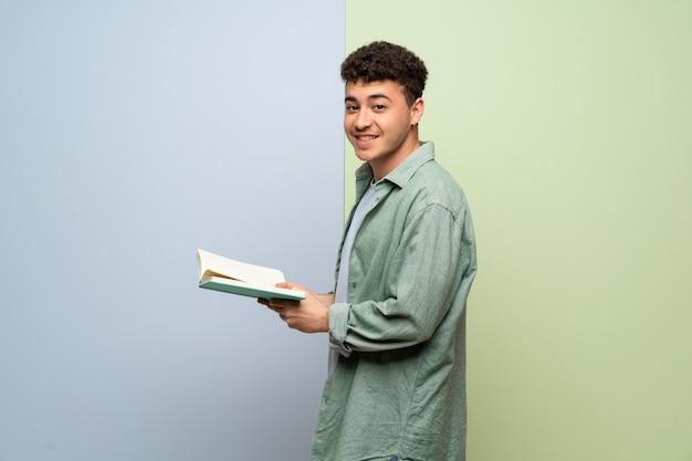 Jovem, azul, verde, segurando, livro, desfrutando, leitura