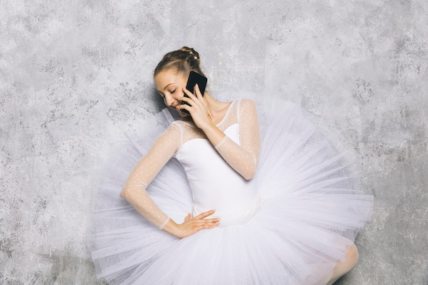 Jovem bailarina bailarina clássica usando telefone celular contra parede rústica