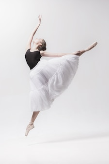 Jovem bailarina clássica isolada no espaço em branco.