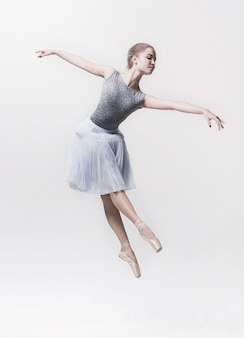 Jovem bailarina clássica isolada no fundo branco.
