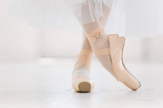 Jovem bailarina, closeup nas pernas e sapatos, em pé na posição de ponta.