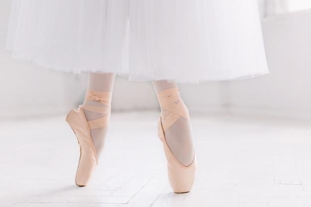 Jovem bailarina, closeup nas pernas e sapatos