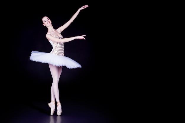 Jovem bailarina com tutu solo dançando e fazendo suporte nos dedos do pé na cena preta escura com piso refletindo
