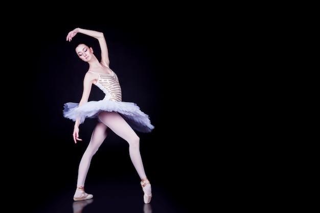 Jovem bailarina com tutu solo dançando na cena preta escura com piso refletindo