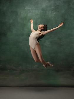 Jovem bailarina concurso graciosa no espaço verde escuro do estúdio