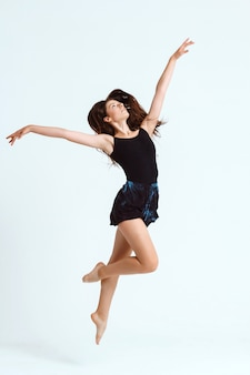 Jovem bailarina contemporânea linda posando sobre parede branca. copie o espaço.