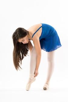 Jovem bailarina curvando-se amarrando os sapatos